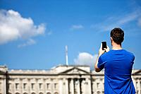 A young man taking a picture of Buckingham Palace