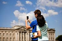 A young couple taking a picture of Buckingham Palace (thumbnail)