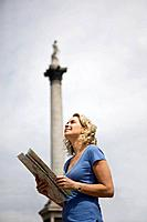 A middle_aged woman standing in Trafalgar Square, looking at a map
