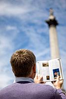 A middle_aged man in front of Nelson's column, looking at a guidebook