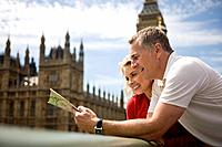 A middle_aged couple standing near the Houses of Parliament, looking at a map