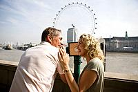 A middle_aged couple using a telescope in front of the London Eye