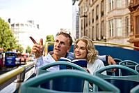 A middle_aged couple sitting on a sightseeing bus, admiring the view