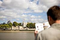 A mid_adult man standing in front of the Tower of London, looking at a guidebook