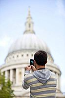 A mid_adult man taking a photograph of St Paul's cathedral