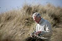 A senior man sitting amongst the sand dunes, pouring a hot drink from a flask