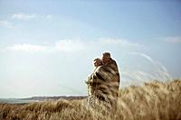 A senior couple standing in sand dunes, wrapped in a blanket