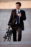 A businessman carrying his folded bicycle to work