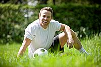 A young man sitting on the grass with a football