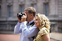 A middle_aged couple taking a photograph