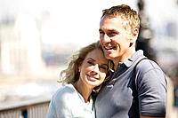 Portrait of a middle_aged couple next to the river Thames embracing