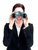 Portrait of a happy young female executive looking through binoculars against white background