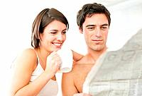 Closeup portrait of an attractive young couple reading newspaper during their breakfast
