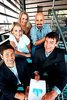 Portrait of smiling group of businespeople sitting together on staircase