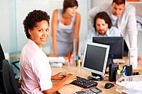 Young business woman working on computer with her team in background