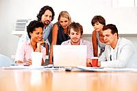 Group of business people looking at laptop in office