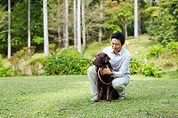 Mid Adult Man with Chocolate Labrador in Park