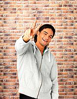 Handsome man standing against brick wall giving peace sign
