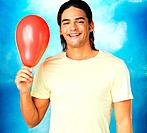 Closeup of happy young man holding red balloon