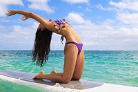Hawaii, Beautiful brunette girl doing yoga on her stand up paddle board