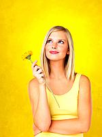 Woman holding flower and looking up against yellow background