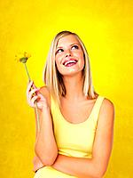 Happy woman holding flower and looking up against yellow background