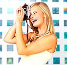 Side view of happy woman taking photo with vintage camera