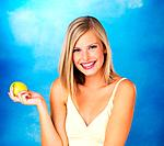 Pretty woman holding apple against blue background