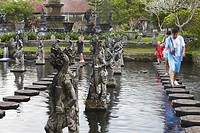 People walking on stepping stones at Taman Tirta Gangga Water Palace, Tirta Gangga, Bali, Indonesia