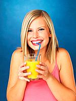 Closeup of pretty woman sipping orange juice against blue background