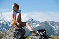 young woman taking a rest sitting on a rock while mountain hiking in summer, Austria, Tyrol, Jerzens