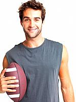 Happy athletic man holding onto football