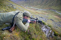 stalker lying on the belly at the edge of a mountain slope aiming down into the valley with his gun, United Kingdom, Scotland, Sutherland, Alladale Wi...