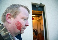 portrait of a stalker with blood on the cheek in front of a station where the shot animals are carved up, United Kingdom, Scotland, Sutherland, Allada...
