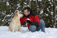 A young man plans with his golden labrador dog in snow during winter, on the Bruce Peninsula, Ontario, Canada.