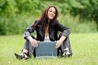 young woman sitting in a meadow with a laptop