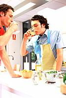 Two Young Men Drinking a Glass of White Wine in Kitchen