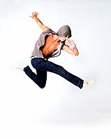 Portrait of young male breakdancer jumping in air against grey background