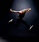 Portrait of young male hip hop dancer jumping in air against grunge background