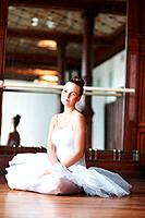 Portrait of a young beautiful ballet dancer resting on wooden floor