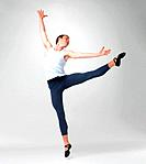 Full length of a male ballet dancer performing against white background