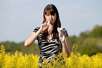 young woman in a rapefield with nasal spray, Germany