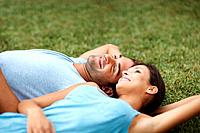 Portrait of a happy young couple lying on grass in a park _ Outdoor