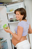 pregnant woman in front of the fridge