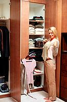 Happy mature woman standing at wardrobe and chooses what can to dress
