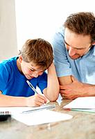 Portrait of a cute little boy doing homework with his father _ Indoor