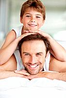 Portrait of a handsome young father and his son on bed