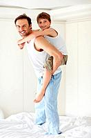 Portrait of a happy young father piggybacking his son on bed