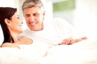 Portrait of happy mature couple lying on bed and looking at each other