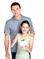 Portrait of a small girl eating fruit salad while standing with her father against white background